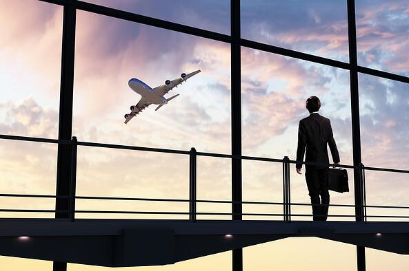 Image of businessman at airport looking at airplane taking off.jpeg